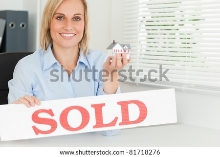 Blonde businesswoman showing miniature house and SOLD sign looking into the camera in her office - stock photo