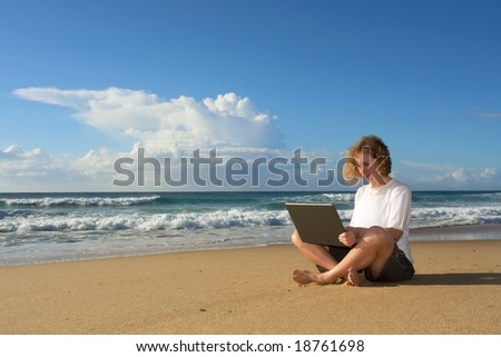 Blonde businesswoman sits with notebook on beach - against dramatic skies. Shot in Sodwana Bay Nature Reserve, KwaZulu-Natal province, Southern Mozambique area, South Africa. - stock photo