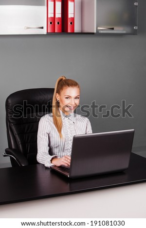 blonde businesswoman typing on laptop at her desk looking at camera in office