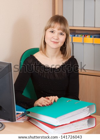 Blonde businesswoman with documents  working in office room
