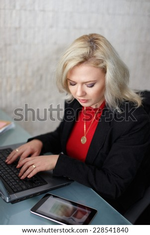 Blonde businesswoman working on laptop, looking on tablet online growth chart - stock photo