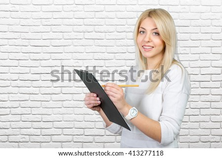 blonde businesswoman writing notes in the clipboard - stock photo