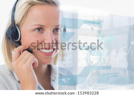 Blonde call center worker using futuristic holographic interface while on a call in office