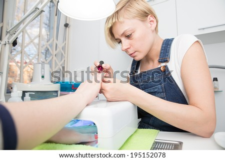 blonde carefully  paints  client nails in UV lamp - stock photo