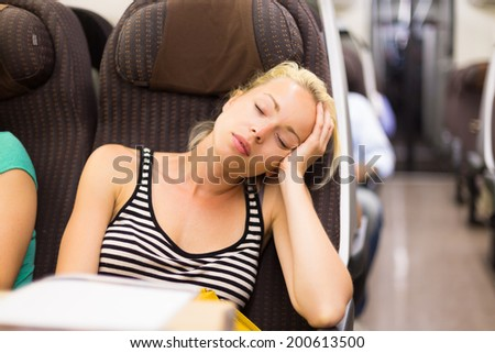 Blonde casual caucasian lady napping while traveling by train. - stock photo
