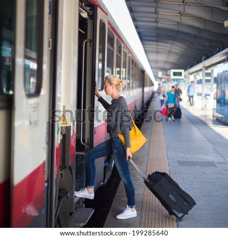 Blonde casual caucasian lady traveling by train. Train full of passengers going to work by public transport at rush hour. - stock photo
