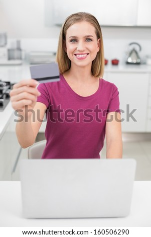 Blonde casual woman using laptop and credit card sitting in kitchen
