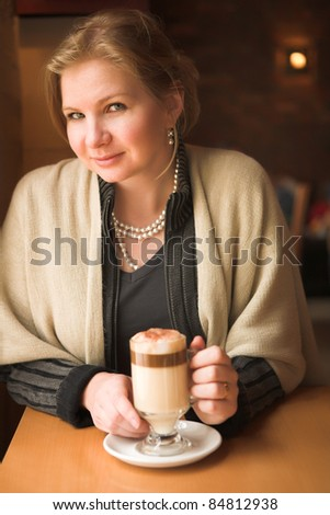 Blonde caucasian adult woman sitting next to a natural light window in the beginning of winter drinking hot cafe latte. Shallow Depth of Field - stock photo