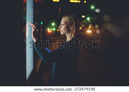 Blonde caucasian businesswoman touching sensitive screen of smart city bus stop in night city with out-of-focus lights, young female doing internet money payment with automated teller machine, filter - stock photo