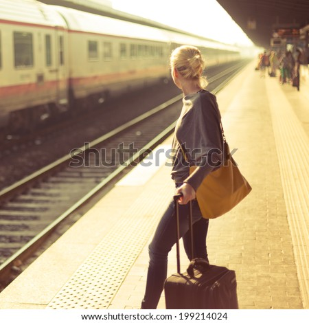 Blonde caucasian woman waiting at the railway station with a suitcase. - stock photo