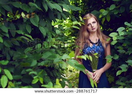Blonde caucasian woman with long straight hair holding a cornflower bouquet posing in the labyrinth of trees