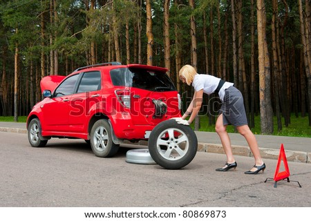 Blonde changing tire on a road - stock photo
