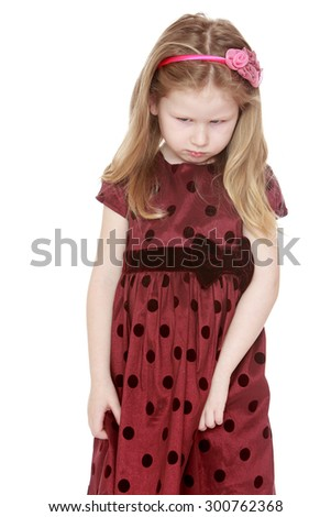 Blonde charming little girl with a headband on his head in a long brown dress with polka dots. The girl was upset, sad she pulls the floors of her dress , close-up-Isolated on white background - stock photo