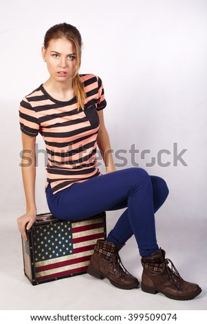 Blonde cheerful young woman is sitting on a suitcase like an American flag. Stars and stripes. Beauty portrait, perfect makeup.  - stock photo