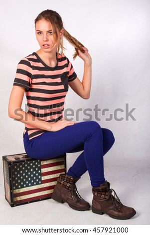 Blonde cheerful young woman is sitting on a suitcase like an American flag. Stars and stripes. Beauty portrait, perfect makeup. dreaming isolated on white background - stock photo