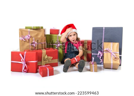 Blonde christmas kid around several presents doing surprise gesture
