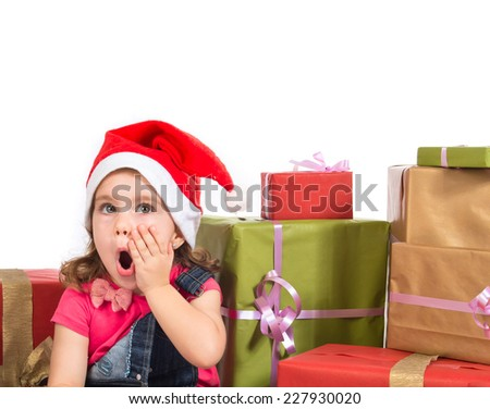 Blonde christmas kid around several presents doing surprise gesture - stock photo