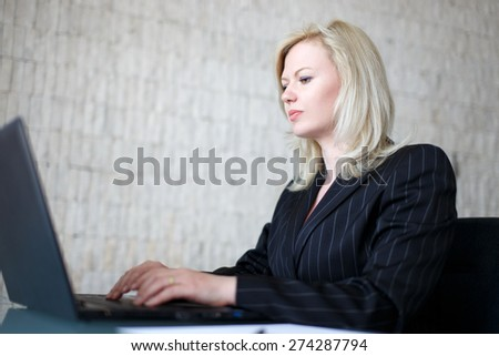 Blonde confident businesswoman typing on laptop - stock photo