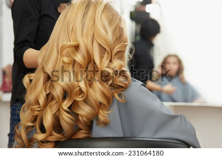 Blonde curly hair. Hairdresser doing hairstyle for young woman in salon - stock photo