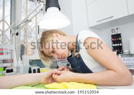 blonde doing manicure under lamp - stock photo