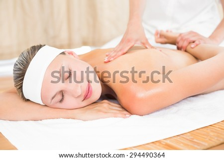 Blonde enjoying a back massage at the health spa
