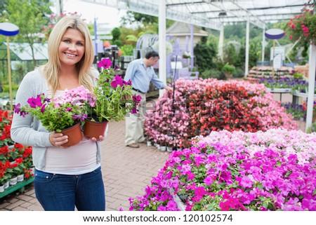 Blonde female customer in garden center while holding flowers - stock photo