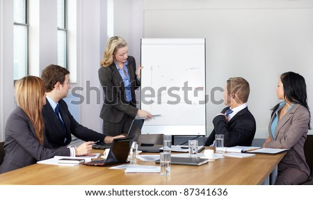 Blonde female present graph on flipchart during business meeting, while 4 more colleagues sits at conference table. - stock photo