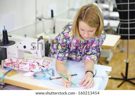 Blonde female tailor draws on patterns near white sewing machine.