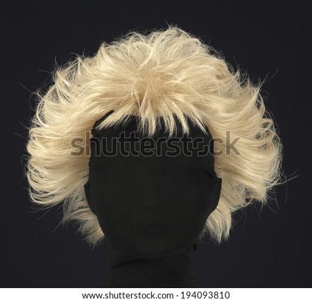 blonde feminine wig on black background and textile mannequin. - stock photo