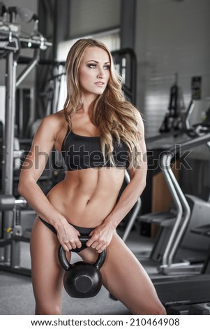 Blonde fitness model posing with kettlebell in gym - stock photo