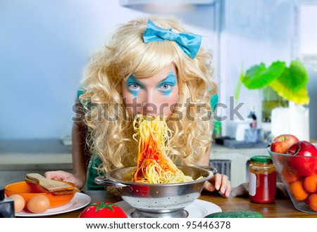 Blonde funny girl on kitchen eating pasta like crazy with blue makeup - stock photo