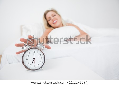 Blonde getting her alarm clock while lying in her bed - stock photo
