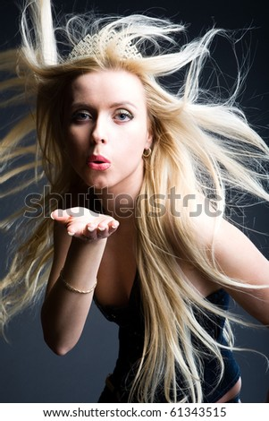blonde girl blowing in her hand - stock photo