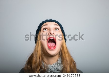 blonde girl catches tongue snowflakes, Christmas and New Year concept, studio photo isolated on a gray background - stock photo