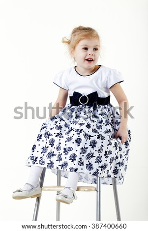 blonde girl child sitting on a chair. Isolated white background.