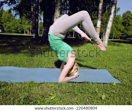 blonde girl doing yoga in green park - stock photo