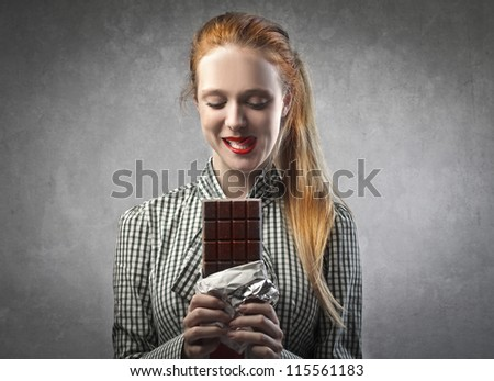 Blonde girl eating a chocolate bar