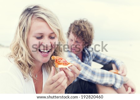 Blonde girl eating pizza on beach. - stock photo