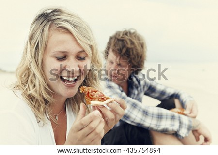 Blonde girl eating pizza on beach Concept