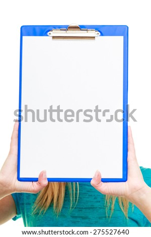 Blonde girl female college student holds clipboard with empty blank covering her face. Isolated on white background - stock photo