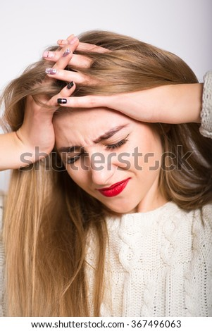 blonde girl has a headache, holding his head, isolated