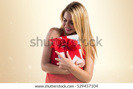 Blonde girl holding a gift on ocher background