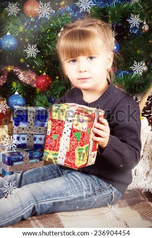 blonde girl holding a gift on the background of the Christmas tree - stock photo