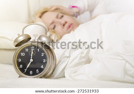 Blonde girl holding hands on her ears, because of alarm clock sound. Selective focus on clock