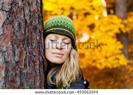 Blonde Girl Hugging Tree Trunk in the Woods. Woman Meditating Outdoors with Closed Eyes and Tree Hug over Yellow Autumn Background. Inspirational Concept Outdoors in Beautiful Nature.