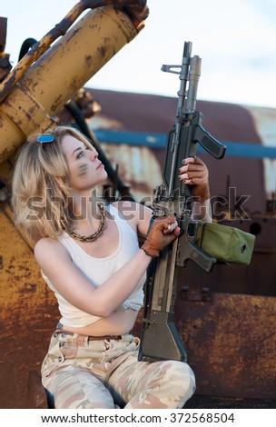 Blonde girl in a military uniform gun reloads - stock photo