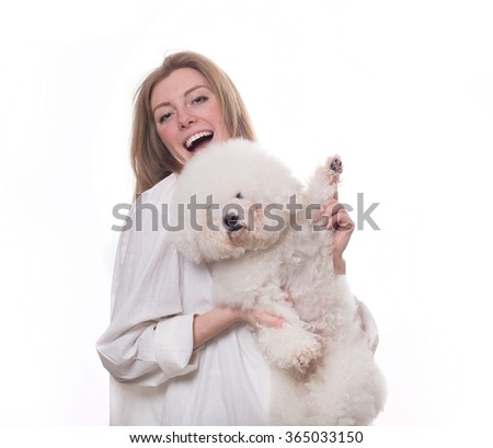 blonde girl in a white gown with a white purebred dogs isolated on a white background. veterinarian. groomer. hairdresser for animals.