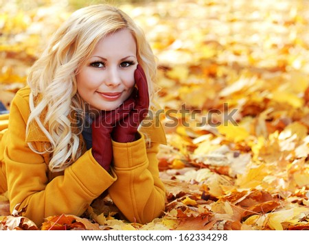 Blonde girl in Autumn Park with Maple leaves. Fashion Beautiful Woman with leather gloves. Fall - stock photo