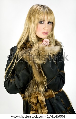 Blonde girl in leather coat on white background  - stock photo