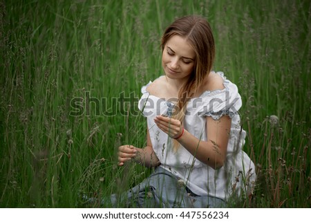 Blonde girl in shorts sitting on the grass outdoors.